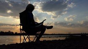 O homem novo senta, lê e escreve suas notas em um Riverbank no por do sol filme