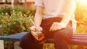 O homem novo senta-se com a garrafa do cidre nas mãos Vista próxima sunlight fotos de stock