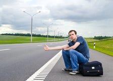 O homem novo senta-se durante na estrada com mala de viagem Imagem de Stock Royalty Free