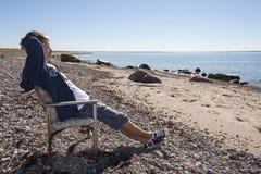 O homem novo senta-se e relaxa-se na cadeira na praia Imagens de Stock Royalty Free