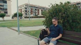 O homem novo senta-se em um banco em um parque video estoque