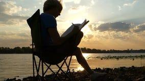 O homem novo senta-se em uma cadeira de dobradura no Riverbank, escreve no por do sol no Slo-Mo video estoque