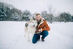 O homem novo senta-se na neve ao lado de um Malamute do Alasca do cão e abraça-se o seu fotografia de stock royalty free