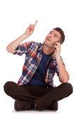 O homem novo senta-se, negociações, pontos e olha-se acima Foto de Stock