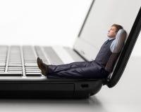 O homem novo senta-se no portátil Imagem de Stock
