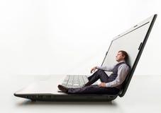 O homem novo senta-se no portátil Fotografia de Stock