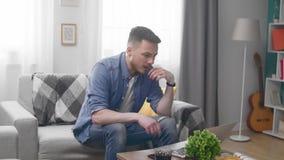 O homem novo senta-se no sofá e fica-se irritado devido às más notícias no portátil filme