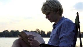 O homem novo senta-se, sorrisos, e escreve-se algo em um Riverbank agradável video estoque