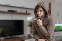 O homem novo sente frio em casa fotografia de stock