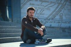 O homem novo studen o livro de leitura fora no dia ensolarado foto de stock royalty free