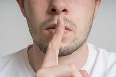 O homem novo tem o dedo nos bordos e em mostrar ser gesto quieto imagens de stock