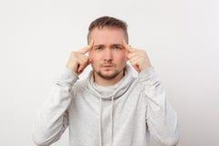 O homem novo tenta concentrar-se duramente e pensar Fotografia de Stock