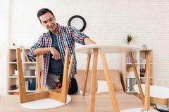 O homem novo tenta-se dobrar seus mesa de centro e tamboretes foto de stock royalty free