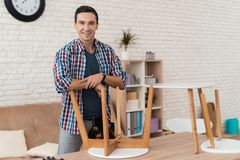 O homem novo tenta-se dobrar seus mesa de centro e tamboretes fotos de stock royalty free