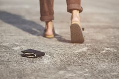 O homem novo tinha perdido a carteira de couro com dinheiro na rua Close-up da carteira que encontra-se no passeio concreto da es foto de stock