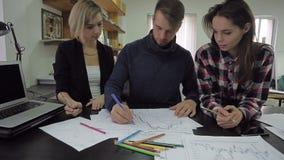 O homem novo tira um gráfico com lápis coloridos, explica algo aos colegas e às folhas fêmeas video estoque