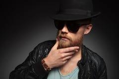 O homem novo toca em sua barba Imagens de Stock