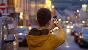 O homem novo toma fotos nas ruas de uma vila video estoque