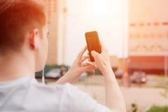 O homem novo toma a imagem usando o telefone exterior Vista próxima, luz solar imagem de stock