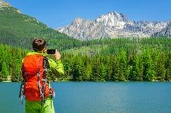 O homem novo toma uma foto do lago da montanha, Eslováquia imagens de stock