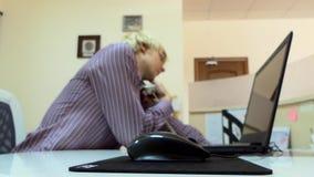 O homem novo trabalha em um portátil em um escritório Toma um telefone de repente video estoque