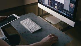 O homem novo trabalha no computador e em uma tabuleta vídeos de arquivo