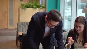 O homem novo traz o milk shake ao colega de trabalho e continuam sua conversação com um portátil no café vídeos de arquivo