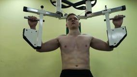 O homem novo treina os músculos peitorais no gym, fazendo a aptidão video estoque