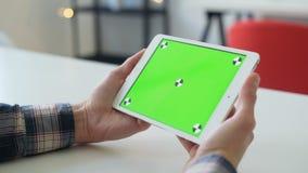 O homem novo usa o smartphone com greenscreen para uma comunicação vídeos de arquivo
