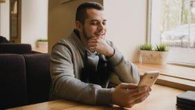 O homem novo usa o telefone em um café Fotos de Stock