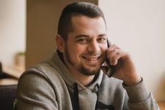 O homem novo usa o telefone em um café Imagem de Stock Royalty Free