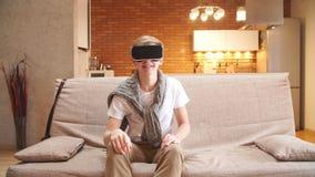 O homem novo usa vidros da realidade virtual na casa, folheando através das páginas virtuais vídeos de arquivo