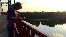 O homem novo vem acima com ideias, põe-nas para baixo em um bloco de notas sobre uma ponte no Slo-Mo filme