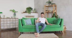 O homem novo vem na sala de visitas, senta-se no sofá verde gerencie na televisão e na observação filme