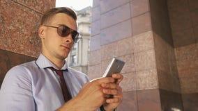 O homem novo verifica seu telefone que está na rua video estoque