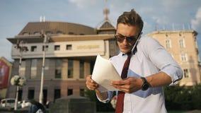 O homem novo verifica seus papéis que estão na rua video estoque