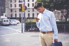 O homem novo vestiu-se na mensagem recebida do equipamento leitura ocasional do operador móvel Fotografia de Stock