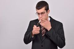 O homem novo vestiu-se no cigarro da iluminação do smoking no estúdio Imagens de Stock