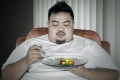 O homem obeso hesitado come a salada no sofá foto de stock royalty free
