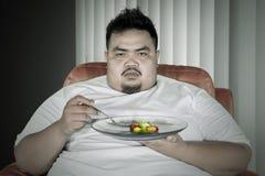 O homem obeso infeliz come a salada no sofá imagem de stock