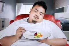 O homem obeso triste come a salada no quarto imagens de stock royalty free