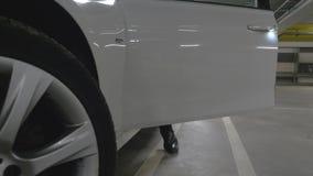 O homem obtém dentro a um carro estacionado em uma garagem filme