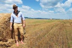 O homem ocasional ao lado do monte de feno olha afastado Imagem de Stock Royalty Free