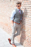 O homem ocasional inclina-se em uma parede de tijolo Fotografia de Stock