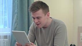 O homem ocasional novo tem uma chamada video através da tabuleta em casa Fotografia de Stock Royalty Free
