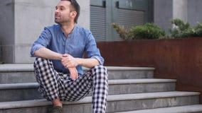 O homem ocasional pensativo que pensa e que senta-se relaxa em escadas vídeos de arquivo