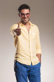 O homem ocasional que sorri mostrando os polegares levanta o gesto Foto de Stock Royalty Free