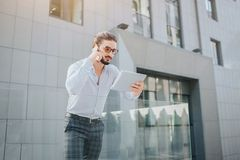 O homem ocupado e considerável está e guarda a tabuleta Olha suas tela e negociações no telefone ao mesmo tempo Este indivíduo é foto de stock