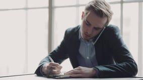 O homem ocupado novo em um terno fala em seu telefone, escuta atentamente, nós e toma notas no mesmo tempo Retrato masculino vídeos de arquivo