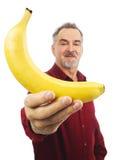 O homem oferece uma banana amarela com braço outstretched fotografia de stock royalty free